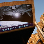 A giant screen shows a view of earth from the Tianhe core module of China's space station, at a shopping mall in Beijing